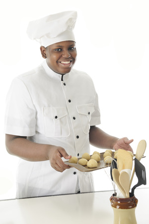 cookie sheet: A young chef happily carrying a cookie sheet of dough balls to bake them in the overn.  On a white background.