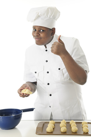 A young chef holding unshaped cookie dough as he looks at the viewer with a definite thumbs up.  On a white background. photo