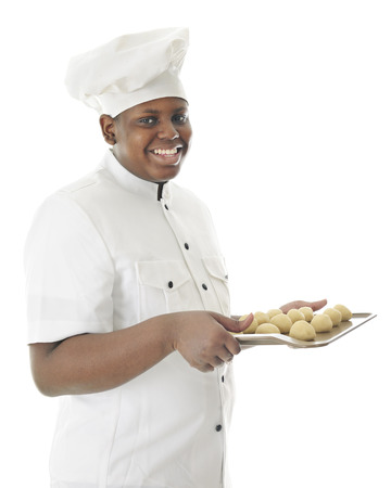 looking at viewer: A young chef happily looking at the viewer as he carries a cookie sheet filled with a dozen balls of dough.  On a white background.
