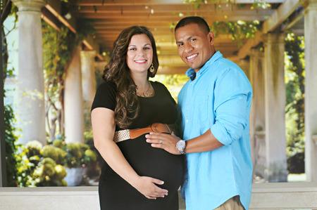 embarazada feliz: Un feliz, expectante joven de pie delante de un sol iluminó pórtico. Foto de archivo