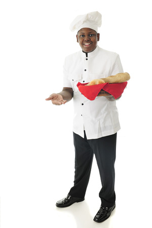 chef: A young African American chef offering the viewer to sample some of his specialty breads.  On a white background.