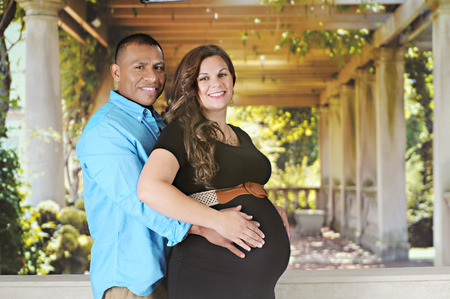 couple lit: A expectant couple happily touching the pregnant belly as tje stamd before a sun lit portico.