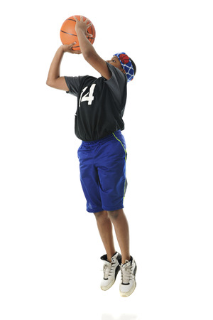 preteen: A preteen athlete making a basketball jump shot.  Includes motion blur.  On a white background.