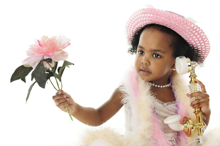 french fancy: Close-up of an adorable two year old diva in pearls, a pink hat, boas and holding a flower while talking on a fancy French phone.  On a white background.
