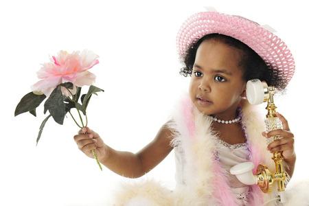 boas: Primo piano di un adorabile bambino di due anni diva in perle, un cappello rosa, boa e in mano un fiore mentre parla su un telefono francese di fantasia. Su uno sfondo bianco.
