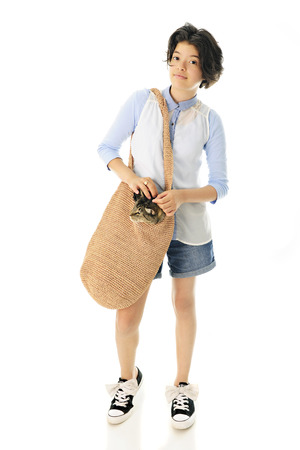 shoulder bag: An attractive young teen taking a walk with her pet cat ipolking his head out of her tan shoulder bag.  Focus is on the girl.  On a white background.