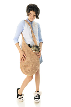 shoulder bag: Full-length image of a pretty young teen carrying her cat in a large, woven shoulder bag.  Focus is on the girl.  On a white background.