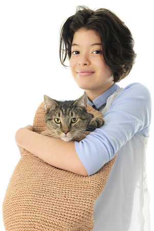 shoulder bag: A young teen girl happily holding her pet Tabby cat in a tan, woven shoulder bag.  On a white background. Stock Photo