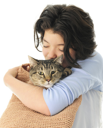 A pretty young teen snuggling (eyes closed) with her pet in a woven shoulder bag.  On a white background.