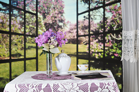 lacey: A small table set with a lacey tablecloth, tea set, a bouquet of lilacs and a small book set before a window opened to a field of blooming lilacs.  Focus on the book.