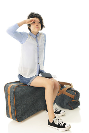 A pretty young teen shielding her eyes searching the skies for her plane as she sits on her suitcase, her passport and boarding pass on her lap.  On a white background.