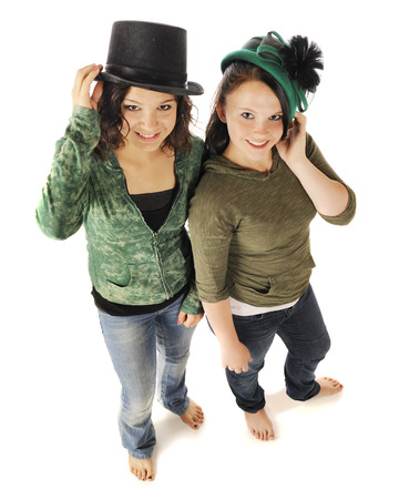 barefoot girls: Overhead view of two barefoot young teen girl looking up at the viewer as they model old time hats.  On a white background. Stock Photo
