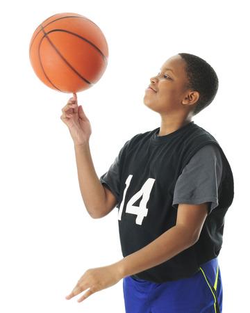 幸いにも彼の人差し指に彼のバスケット ボールの回転プレティーンの少年。 モーション ブラーのボールを白い背景の上。 写真素材