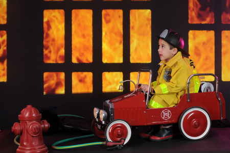 exclaiming: A preschool fireman sitting in his vintage firetruck exclaiming about the blaze he sees through nighttime windows.