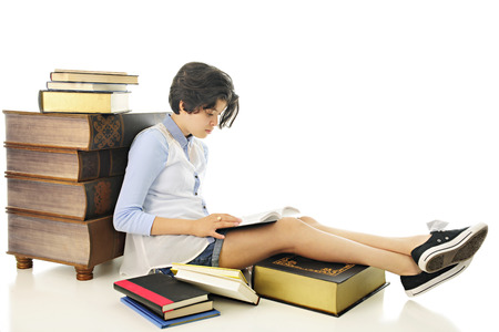 intrigued: An attractive young teen reading one of the books that surround her.  On a white background. Stock Photo