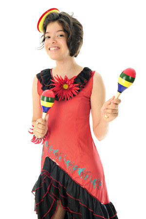 mexican dress: An attractive young teen happily wearing a red and black Mexican dress, a tiny sombrero and shaking colorful maracas.  On a white background.