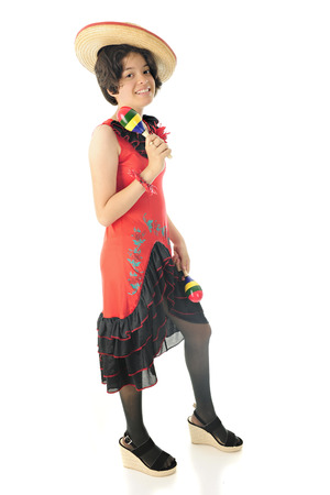 mexican dress: A pretty young teen shaking maracas while happily posing in a red and black Mexican dress and sombrero.  On a white background.