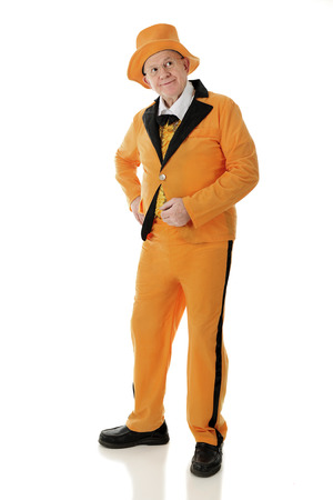 lapels: Full length image of a standing senior adult man looking up and off to the side in his orange and black tuxedo and hat.  On a white background.