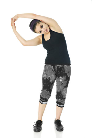 arching: A pretty teen stretching out in her black and white workout clothes.  On a white background.