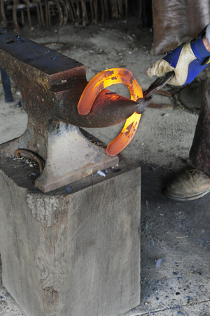 horse shoe: The gloved hand of a blacksmith holding a red hot horse shoe on an anvil where he will hammer it into shape.