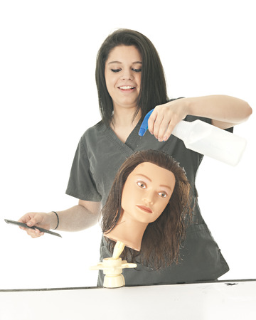 cosmetologist: An attractive student cosmetologist happily spraying her practice head with water.  On a white background. Stock Photo