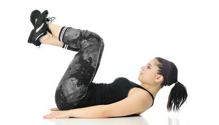 A pretty teen girl doing a lower ab exercise in her workout outfit -- on back, hands flat on floor, legs and head raised.  On w hite background. Stock Photo
