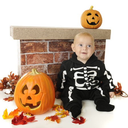 An adorable baby skeleton sitting by a short brick wall and surrounded with colorful leaves and two Halloween pumpkins.  On a white background.