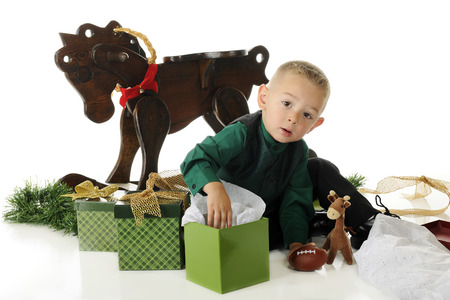 An adorable preschooler dressed up for Christmas, surrounded by gifts.  He's looking up as he digs into one box.  On a white background. photo