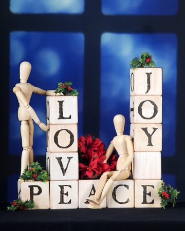 alphabet blocks: Love, Joy and Peace spelled out with rustic alphabet blocks in front of a night-time window.  Two mannequins, holly and a small bouquet of poinsettias adorn the blocks.