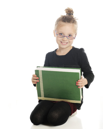 looking at viewer: An adorable elementary girl looking studiously at the viewer over her glasses.   He holds a giant textbook on her lap.  On a white background.