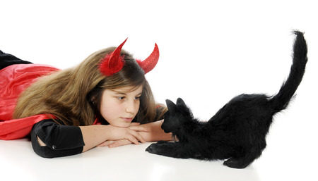 tween: A tween devil staring eye-to-eye with a big black Halloween cat.  Isolated on white.