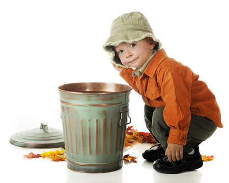 en cuclillas: Un niño en edad preescolar adorable en los colores del otoño en cuclillas al lado de un pequeño bote de basura mientras se limpia las hojas de otoño caidas. Sobre un fondo blanco. Foto de archivo