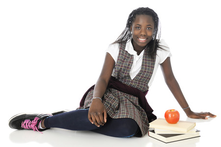 young schoolgirl: A happy tween scholgirl relaxed on the floor in her school uniform, a small stack of books by her side.   On a white background.