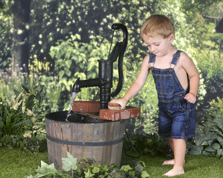 scrubbing: An adorable barefoot 2 year old scrubbing bricks outside by an old water pump.