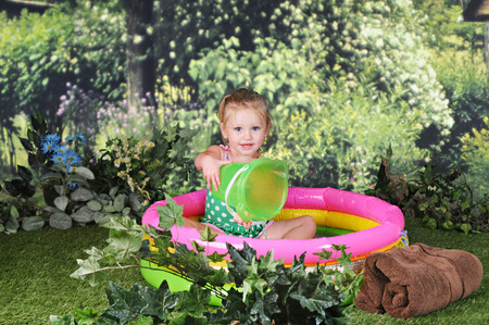 kiddie: An adorable two year old outside happily playing in a small kiddie pool.