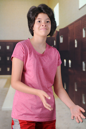 locker room: A pretty young teen anticipating a tossed ball in her school locker room.  Motion blur on her hands. Stock Photo