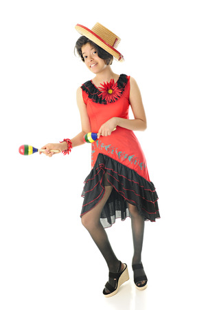 mexican dress: A young teen girl dancing in her red and black Mexican dress and hat, happily accompanying the beat with colorful maracas.  On a white background.