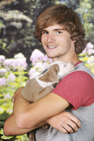 snuggling: An older teen boy happily snuggling with his baby pit bull.