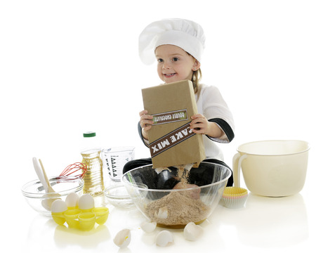 dumping: An adorable preschool chef happily dumping cake mix into a bowl, while surrounded by other cake-making supplies.  On a white background.