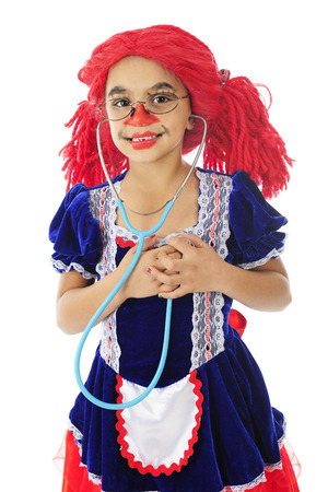 rick rack: A living young rag doll happily listening to her heart with a stethoscope.  On a white background.