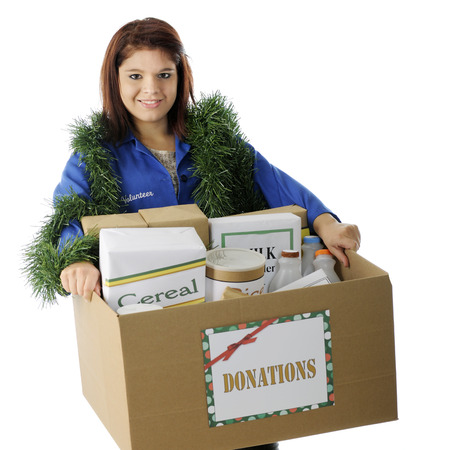 volunteerism: An attractive young volunteer carrying a box of food donations for the holidays.  On a white background. Stock Photo