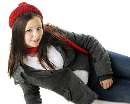 An attractive preteen reclined in her jacket and red winter hat and scarf.  On a white background. photo