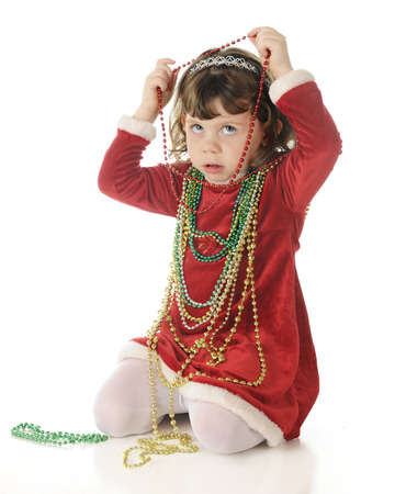 strands: An adorable, dressed up preschooler, worriedly looking up as shes putting strands of Christmas beads around her neck.  On a white background,.