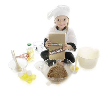 dumps: An overhead view of a toddler chef surrounded by baking supplies as she dumps a box of cake mix into a clear bowl.  On a white background.