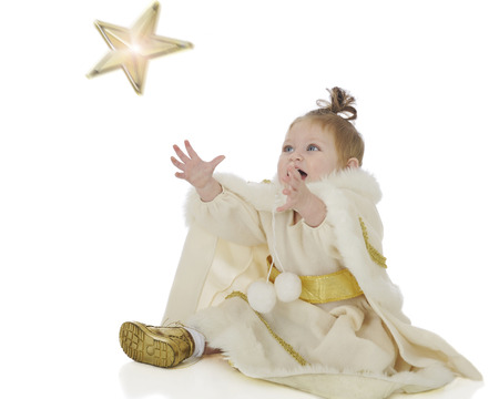 reaching up: An adorable baby snow princes delightedly reaching up to catch a falling star.  Motion blur on the star.  On a white background. Stock Photo