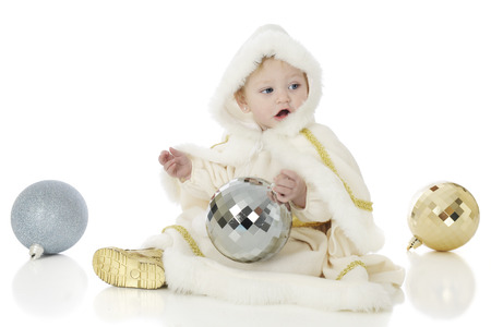 christmas bulbs: An adorable baby snow princess playing with oversized Christmas bulbs.  On a white background.