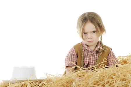 An angry preschool cowgirl sitting behind a pile of hay with her hat nearby.  On a white background with space for your text over her hat. Stock Photo