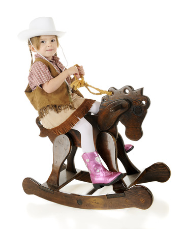 An adorable preschool cowgirl happily riding her wooden rocking horse.  On a white background.