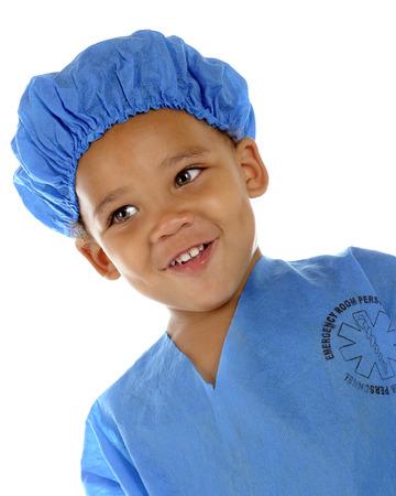 """niños negros: Close-up retrato de una, preescolar """"doctor"""" adorable en batas de color azul. Sobre un fondo blanco."""