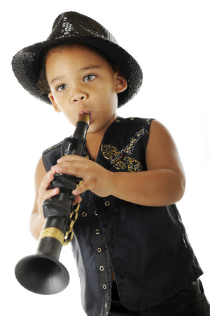 fedora: An adorable preschooler playing a toy clarinet in his sparkly fedora and black leather jacket.  On a white background.